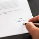 A hand writing a signature