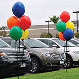 Balloons decorating a car lot.