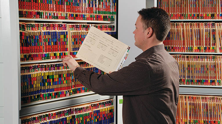 Man filing information using ColorFile Filing System.
